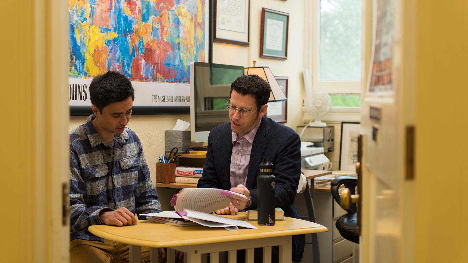 Advisor consulting with a student in their office
