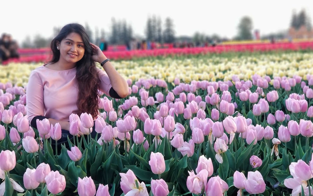 Student sitting in a field of tulips