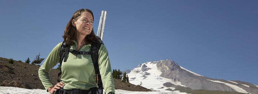woman smiling standing on a mountain top