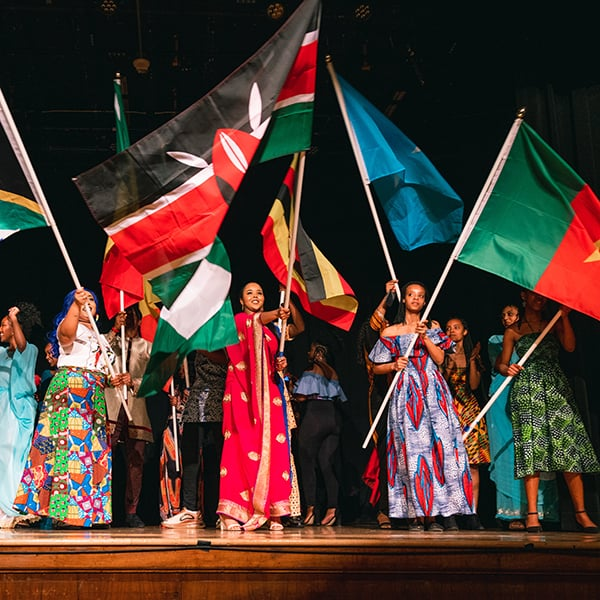 Students on stage waiving flags from African countries.
