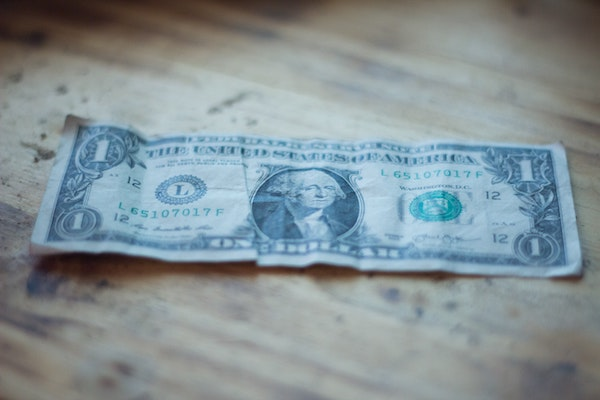 a US dollar bill on a wood floor