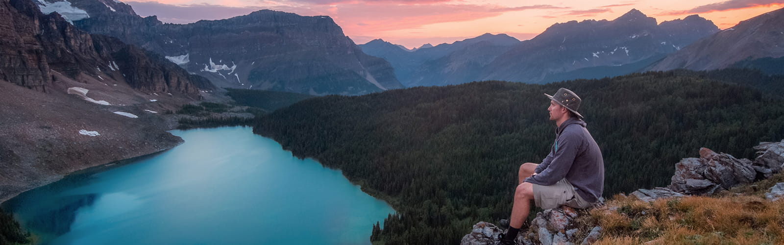 Person sitting on a mountainside overlooking a lake with a sunset in the background