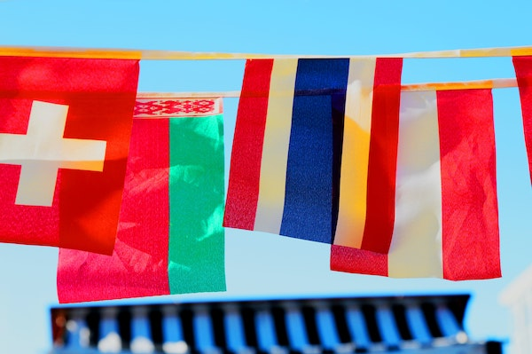 flags of various nations hanging on a line with a blue sky background
