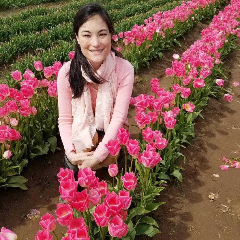 Heather sitting in a field of tulips